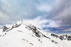 Paesaggio di inverno Picchi di alta montagna innevati sotto i cieli panoramici nuvolosi in Europa Immagine Stock
