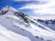 Paesaggio di inverno Picchi di alta montagna innevati sotto i cieli panoramici nuvolosi in Europa Fotografie Stock Libere da Diritti