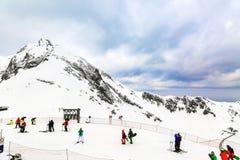 Paesaggio di inverno Picchi di alta montagna innevati sotto i cieli panoramici nuvolosi in Europa Sciatori e snowboarders in disc Fotografie Stock