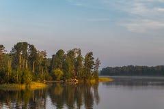 Paesaggio di mattina su un lago con le isole ed i pini fotografia stock libera da diritti