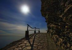 Paesaggio di notte con il mare, la luna e le rocce fotografia stock