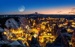 Paesaggio di notte del villaggio di Goreme, Turchia, con una luna piena immagini stock libere da diritti
