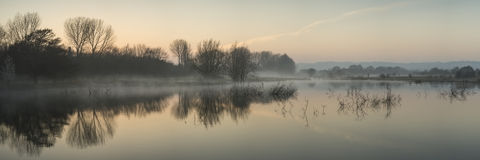 Paesaggio di panorama del lago in foschia con incandescenza del sole ad alba Immagine Stock