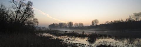 Paesaggio di panorama del lago in foschia con incandescenza del sole ad alba Immagini Stock
