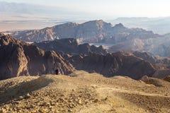 Paesaggio di riposo di seduta del deserto del bordo della montagna del turista di viaggiatore con zaino e sacco a pelo della donn Fotografia Stock