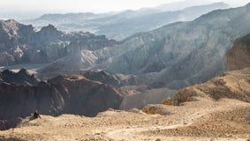 Paesaggio di riposo di seduta del deserto del bordo della montagna del turista di viaggiatore con zaino e sacco a pelo della donn Immagine Stock