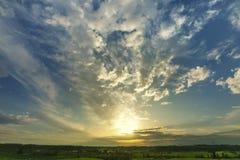 Paesaggio di tramonto con il cielo e le nuvole, molla dell'erba verde largamente Fotografia Stock