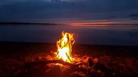 Paesaggio di tramonto con la fiammata bruciante di legno in falò, lago tranquillo e cielo blu di rosa bello immagini stock