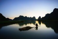 Paesaggio di tramonto con pesca del pescatore sul lago e sulla montagna in Cao Bang, Vietnam fotografie stock
