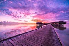 Paesaggio di tramonto dell'isola delle Maldive Nuvole variopinte e cielo con le ville di lusso dell'acqua ed il pilastro di legno Immagine Stock