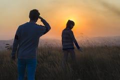 Paesaggio di tramonto della ragazza dell'uomo Fotografia Stock
