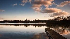 Paesaggio di tramonto sopra il molo sul lago Immagini Stock Libere da Diritti