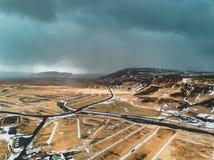 Paesaggio di vista aerea dell'Islanda con neve e nuvole, via ed erba gialla e verde fotografie stock libere da diritti