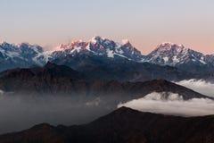 Paesaggio drammatico con i picchi nevosi che aumentano sopra fotografie stock libere da diritti