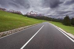 Paesaggio drammatico con la strada verso le nuvole pesanti Fotografie Stock