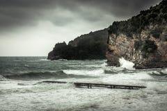 Paesaggio drammatico con le scogliere sulla riva di mare durante la tempesta con le grandi onde tempestose ed il cielo drammatico fotografia stock