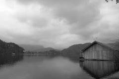 Paesaggio drammatico di inverno con la rimessa per imbarcazioni di legno sul lago in bianco e nero Fotografie Stock Libere da Diritti