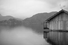Paesaggio drammatico di inverno con la rimessa per imbarcazioni di legno sul lago isolato in bianco e nero Fotografie Stock