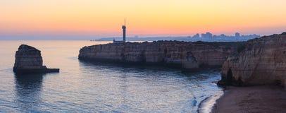 Paesaggio e faro di tramonto della costa di mare Fotografia Stock