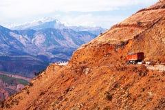 Paesaggio fantastico della cresta rossa della montagna al crepuscolo, il camion rosso che guida su una strada della montagna, il  immagini stock