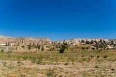 Paesaggio fantastico di Cappadocia turco e dei cavalieri a cavallo nella distanza fotografie stock libere da diritti