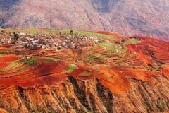 Paesaggio fantastico, vecchio villaggio scenico variopinto di terra rossa ad alba, ambiti di provenienza rossi della montagna Il  immagine stock