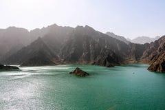 Paesaggio geologico della diga di hatta caratterizzato dalle montagne asciutte e rocciose e dal lago fra le montagne di paesaggio fotografia stock libera da diritti