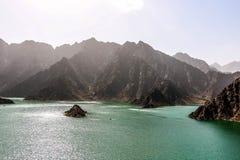 Paesaggio geologico della diga di hatta caratterizzato dalle montagne asciutte e rocciose e dal lago fra le montagne di paesaggio immagini stock