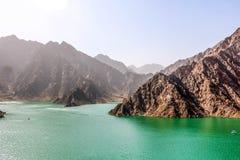 Paesaggio geologico della diga di hatta caratterizzato dalle montagne asciutte e rocciose e dal lago fra le montagne di paesaggio fotografie stock libere da diritti