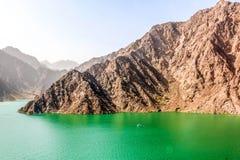 Paesaggio geologico della diga di hatta caratterizzato dalle montagne asciutte e rocciose e dal lago fra le montagne di paesaggio fotografie stock