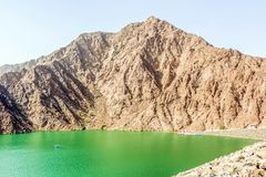 Paesaggio geologico della diga di hatta caratterizzato dalle montagne asciutte e rocciose e dal lago fra le montagne di paesaggio fotografia stock