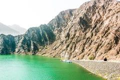 Paesaggio geologico della diga di hatta caratterizzato dalle montagne asciutte e rocciose e dal lago fra le montagne di paesaggio immagine stock