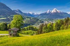 Paesaggio idilliaco della molla nelle alpi con il chalet tradizionale della montagna Immagini Stock Libere da Diritti