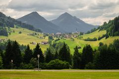 Paesaggio idilliaco della montagna con un piccolo villaggio e montagne nei precedenti fotografie stock libere da diritti
