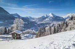 Paesaggio idilliaco di inverno nelle alpi con la casetta della montagna Fotografie Stock