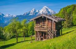 Paesaggio idilliaco di primavera nelle alpi con la casetta tradizionale della montagna Immagine Stock Libera da Diritti