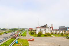 Paesaggio industriale con gli stabilimenti chimici, i tubi e le colonne Sotto è un trattore arancio Il fumo viene dal reattore immagini stock