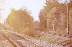 Paesaggio industriale di autunno Ferrovia che retrocede nella distanza fra gli alberi verdi e gialli di autunno immagini stock
