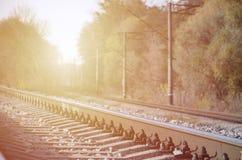 Paesaggio industriale di autunno Ferrovia che retrocede nella distanza fra gli alberi verdi e gialli di autunno immagine stock