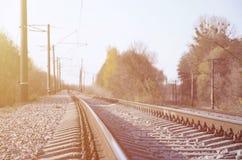 Paesaggio industriale di autunno Ferrovia che retrocede nella distanza fra gli alberi verdi e gialli di autunno fotografie stock libere da diritti
