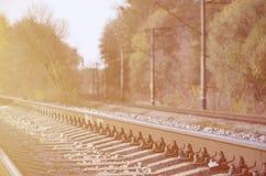 Paesaggio industriale di autunno Ferrovia che retrocede nella distanza fra gli alberi verdi e gialli di autunno fotografia stock libera da diritti