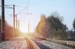 Paesaggio industriale di autunno Ferrovia che retrocede nella distanza fra gli alberi verdi e gialli di autunno immagini stock libere da diritti