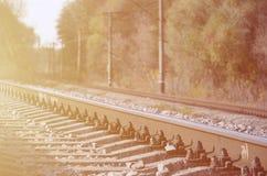 Paesaggio industriale di autunno Ferrovia che retrocede nella distanza fra gli alberi verdi e gialli di autunno fotografia stock