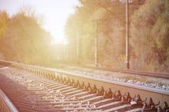 Paesaggio industriale di autunno Ferrovia che retrocede nella distanza fra gli alberi verdi e gialli di autunno fotografie stock