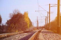 Paesaggio industriale di autunno Ferrovia che retrocede nella distanza fra l'albero verde e giallo di autunno immagine stock libera da diritti