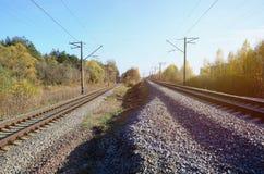 Paesaggio industriale di autunno Ferrovia che retrocede nella distanza fra l'albero verde e giallo di autunno fotografie stock