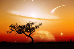 Paesaggio irreale della siluetta sola dell'albero con il pianeta e la galassia immagini stock