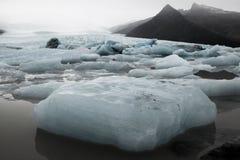Paesaggio islandese meraviglioso della natura Alte montagne, neve, riwer della montagna e pascolo verde Immagini Stock