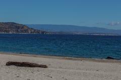 Paesaggio italiano Cielo blu e mare Legno nella parte anteriore sulla spiaggia e sulle montagne nel fondo Nubi Immagine Stock Libera da Diritti