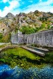 Paesaggio Mediterraneo Scogliere sporgentesi, mura di cinta medievali e fiume Fotografia Stock
